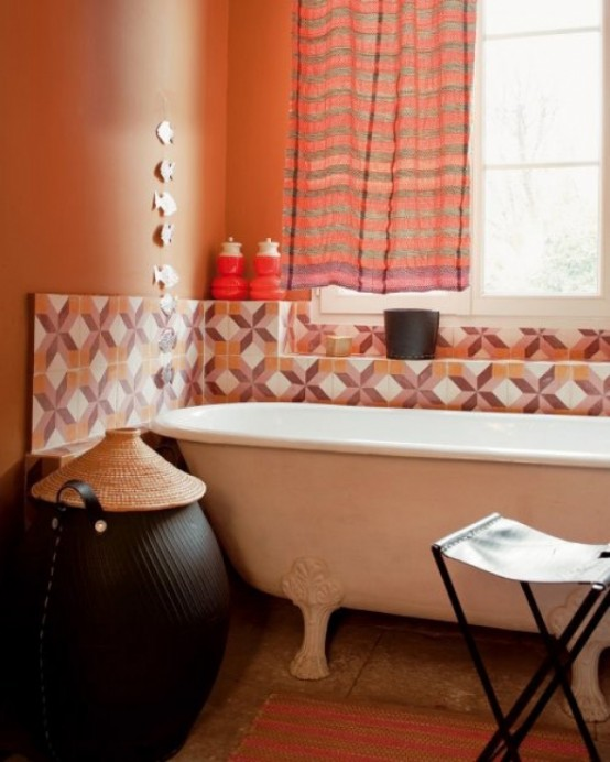 rust-colored walls, bright geometric tiles with rust and burgundy touches, orange striped curtains and a rug