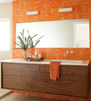 a bright orange tile wall is accents the dark stained wooden vanity and makes it stand out a lot