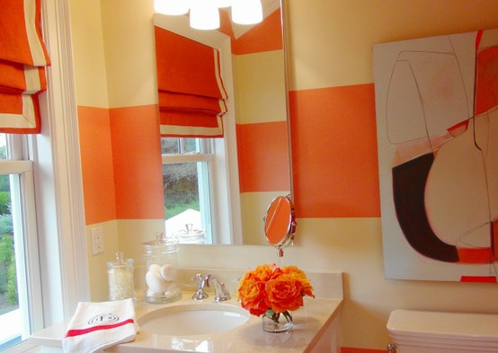orange stripes on the walls, an orange shade, artworks and a floral arrangement for bright touches in the neutral space