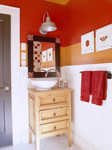 orange and rust colored walls make this bathroom bright, fun and bold, white tiles and a wooden vanity calm down the space