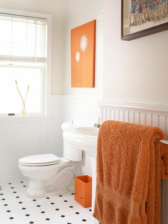 add bright orange touches with an artwork, a litter box and some towels - it's easy to spruce up a neutral space with just some items