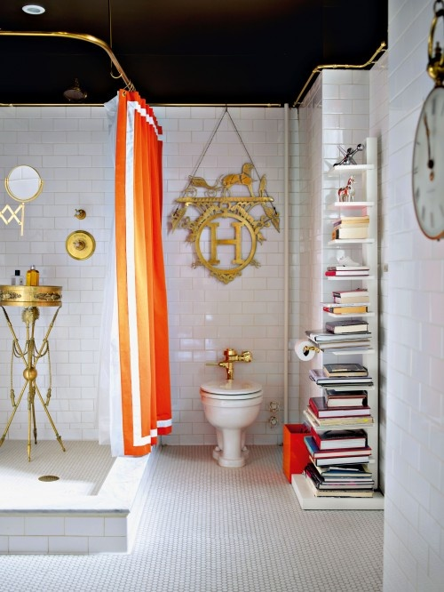 a whimsy art deco bathroom in black, white and gold and an orange curtain and litter box for a more modern and bright touch