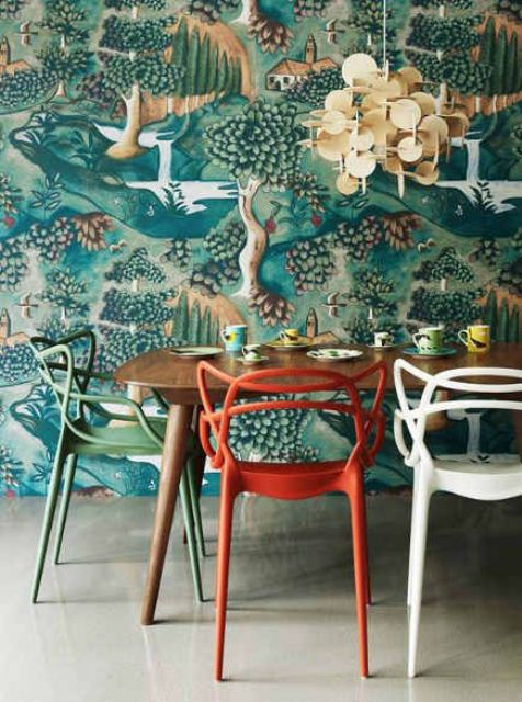 a quirky dining space done with bold flora and fauna print wallpaper, colorful chairs and a sequin chandelier