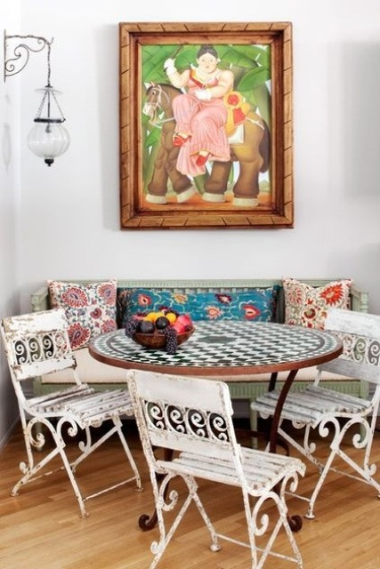 a colorful eclectic space with a bright artwork, mismatching printed pillows, white forged chairs and a checked table