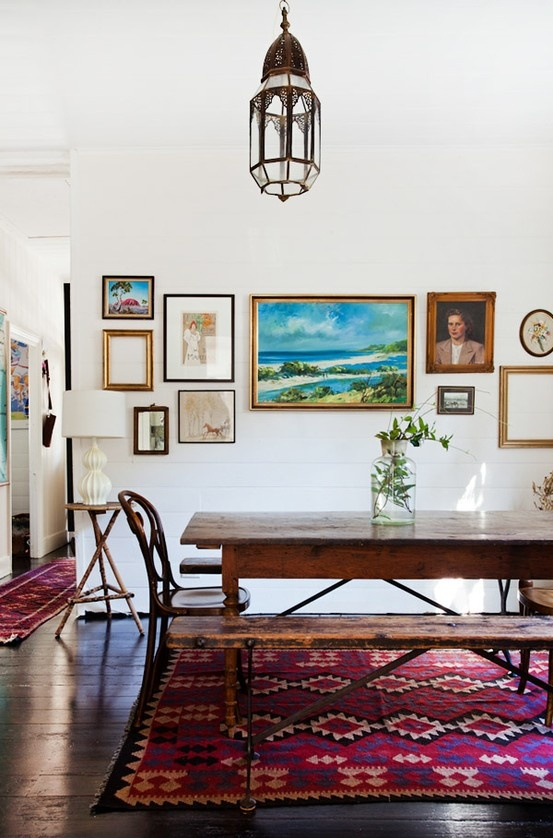 a boho dining room with a bold red rug, a Moroccan lamp, dark staiend furniture and a gallery wall