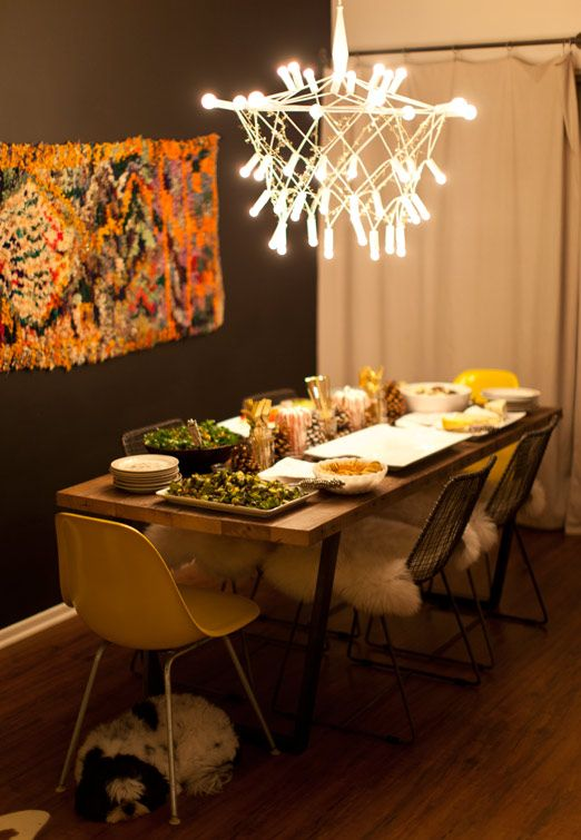 a boho dining space with a yarn artwork, a catchy modern chandelier, faux fur and a wooden table