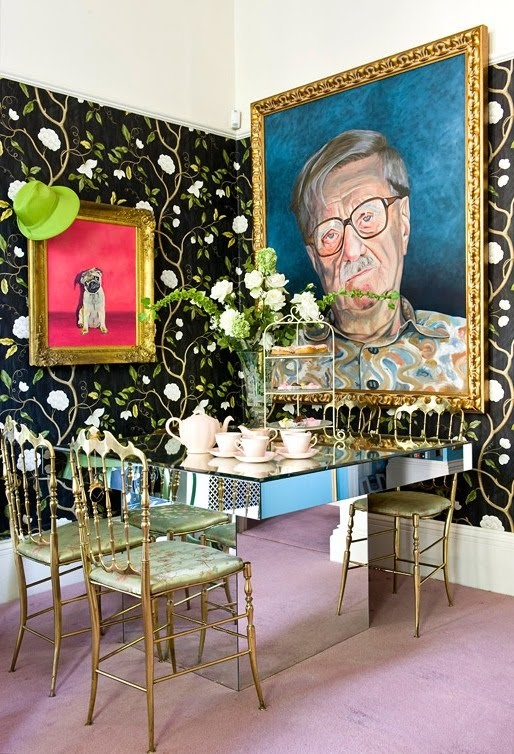 a whimsy colorful dining room with fun artworks, a mirror table and glam gold chairs