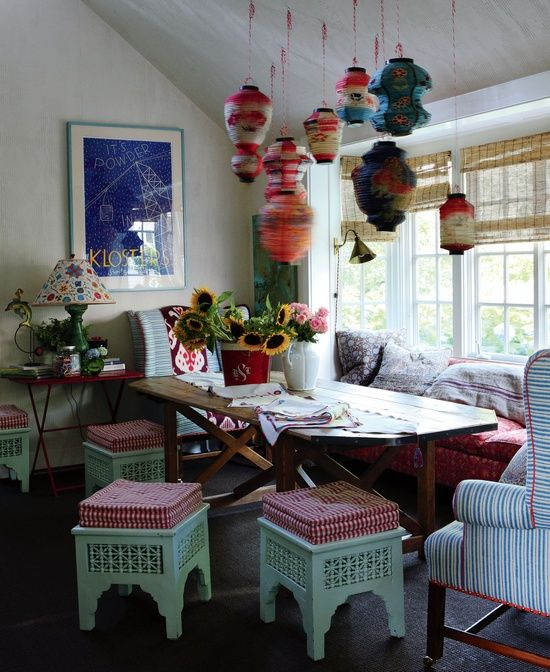 a colorful boho rustic dining room with bright yarn lamps, carved wooden furniture with upholstery and a stained wooden table