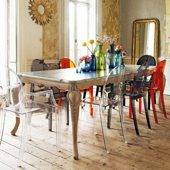 a bright eclectic dining room with colorful mismatching chairs, neutral and wallpaper walls, large mirrors and a vintage table