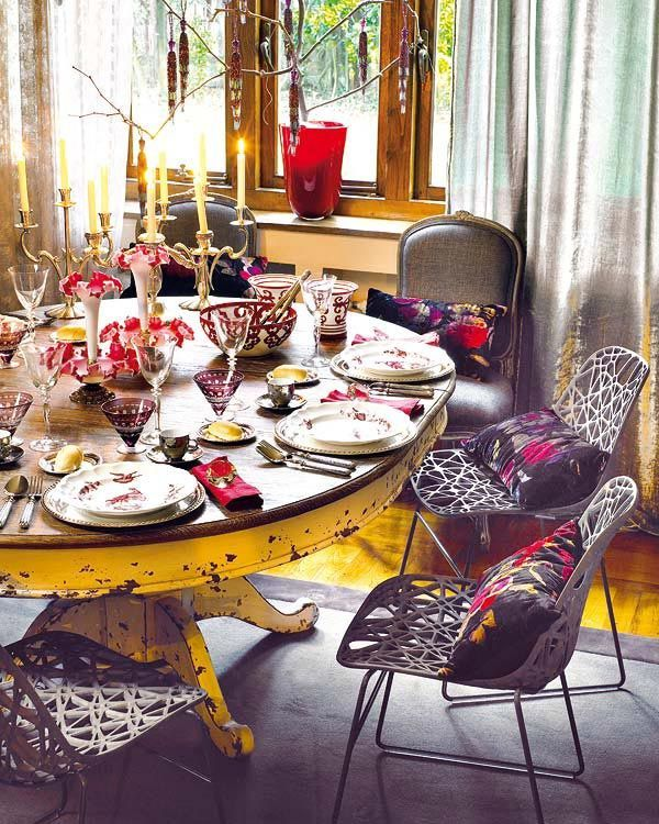 a colorful boho dining room with a shabby chic table, catchy chairs, candles and colorful vases and pots