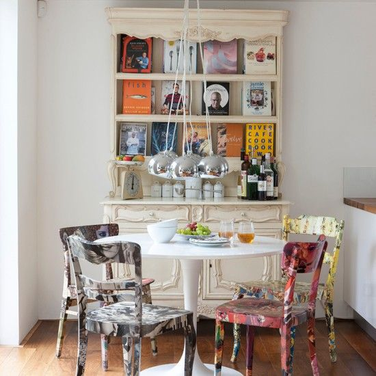 a vintage meets shabby chic dining room with mismatching bright chairs, a chic bookcase and a simple round table