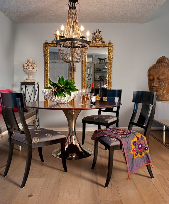 a modern dining room with chic furniture, a refined chandelier, an oversized mirror in a gold frame and an Asian statue head