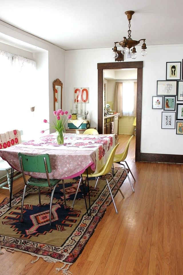 a colorful boho dining space with a hairpin leg table, mismatching chairs, a vintage chandelier and bright boho textiles