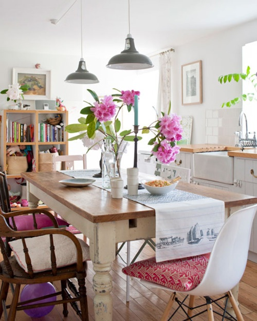 a bright rustic boho dining space with a rustic table, wood and whte plastic chairs and colorful textiles