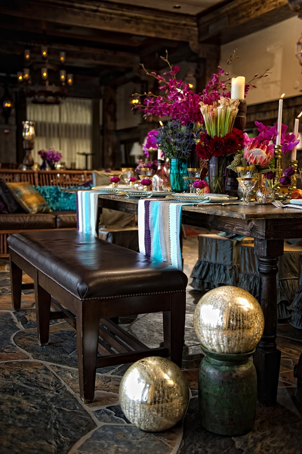 a moody Moroccan dining space with dark furniture, bright blooms, metallics and colorful boho textiles