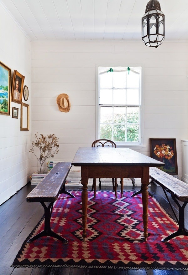 a bright boho dining space with a bold Moroccan rug, dark stained furniture and a pendant Moroccan lamp