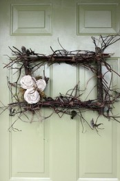 a twig and stick rectangle wreath with moss and fabric blooms is a cool decoration that will make the porch look vintage
