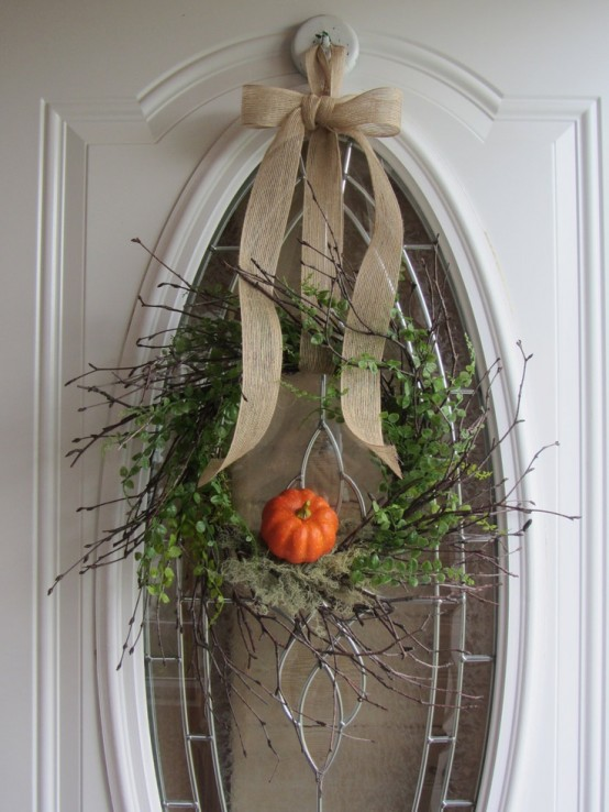 a cool twig fall wreath with greenery, moss, a faux pumpkins and a burlap bow on top is a cool fall decoration
