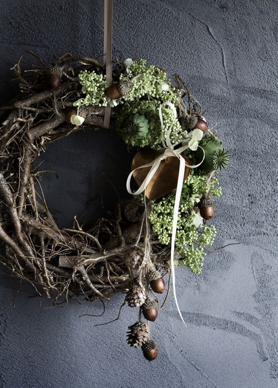a wild twig and stick fall wreath with greenery, acorns, pinecones and nuts and a bow is a very woodland-inspired piece