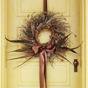 a lush twig fall wreath with nuts, acorns, feathers and a silk ribbon bow will bring a boho feel to the porch