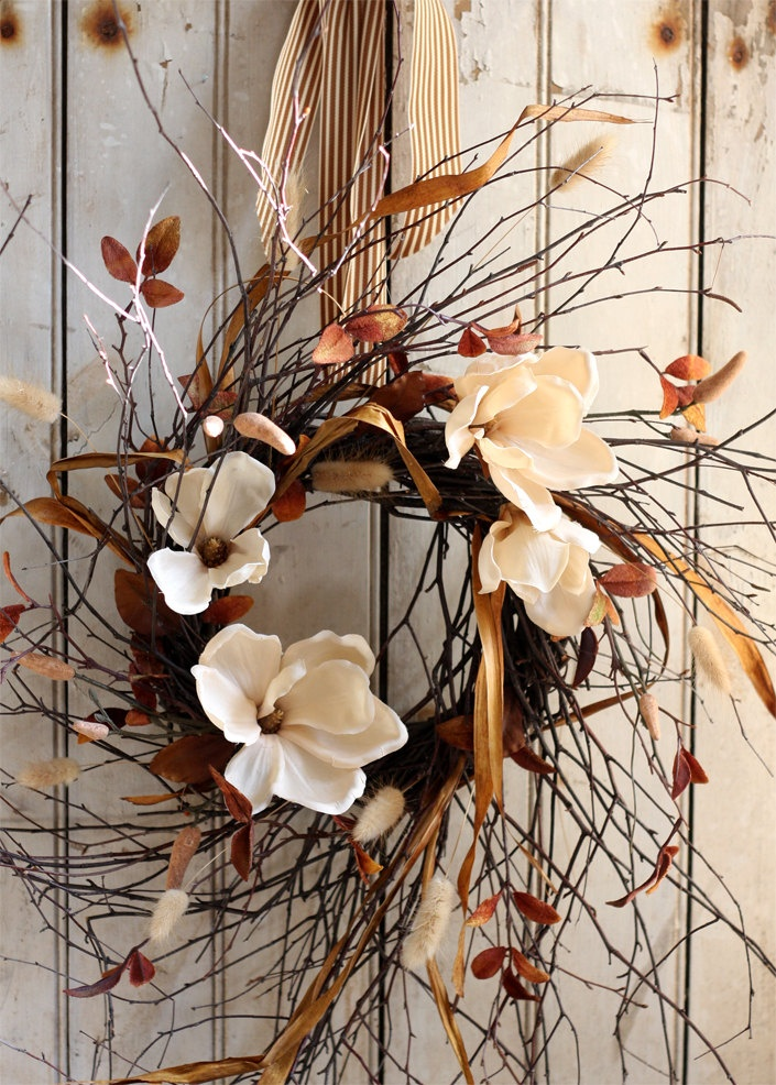 a chic twig fall wreath with white blooms, dried leaves, amber ribbons and a striped ribbon is a cool dried fall decoration