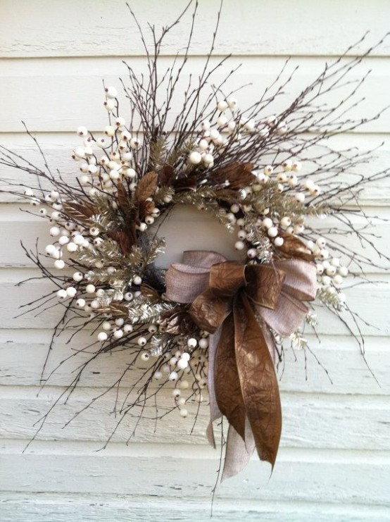a textural twig wreath with faux berries, brown leaves, two large bows and silver branches for fall to winter period