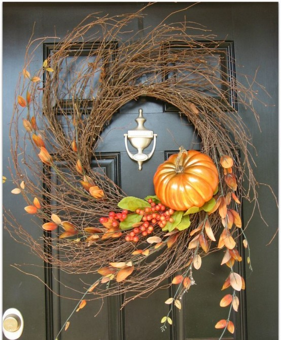 a large textural twig wreath with berries, leaves, greenery and a faux pumpkin is a cool fall decoration