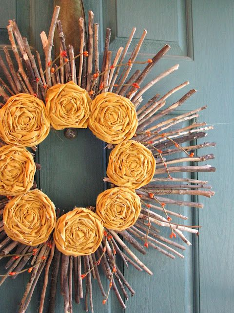 a stick and twig fall wreath with berries and orange fabric flowers is a creative rustic decoration