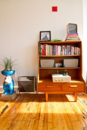 a funky bright wooden bookcase with open shelves and drawers features much storage space and adds color