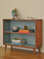 a box shaped mid-century modern bookcase with muted blue lining looks chic and adds a sutble touch of color