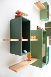 a wall-mounted bookcase in muted green shades with natural-colored shelves features much storage space in a creative way
