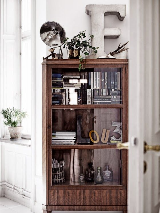 a mid century modern wooden bookcase with glass covered compartments looks rather lightweight and you won't need to dust the shelves every time