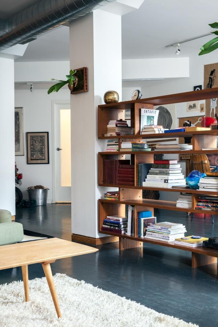 a rich stained wood bookcase made of long boxes doubles as a space divider without looking bulky