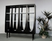 an unusual dark wood bookcase with curves and cutouts plus tall legs will make a statement