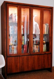 a large redwood bookcase with glass doors and soem storage space plsu glass shelves inside