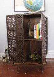 a dark-colored mid-century modern bookcase with laser cut doors and shelves inside