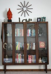 a rich colored wooden bookcase with glass doors features unique curved frames and tall legs