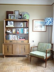 a neutral-colored wooden bookcase with open shelves, some drawers and a cabinet space is traditional for mid-century modern spaces