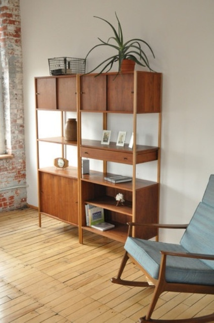 a rich-stained mid-century modern bookcase with closed cabinets, drawers and open shelving