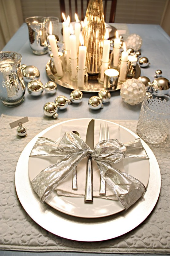a white and metallic winter table setting with metallic ornaments, lots of candles, white and mother of pearl plates and a ribbon bow