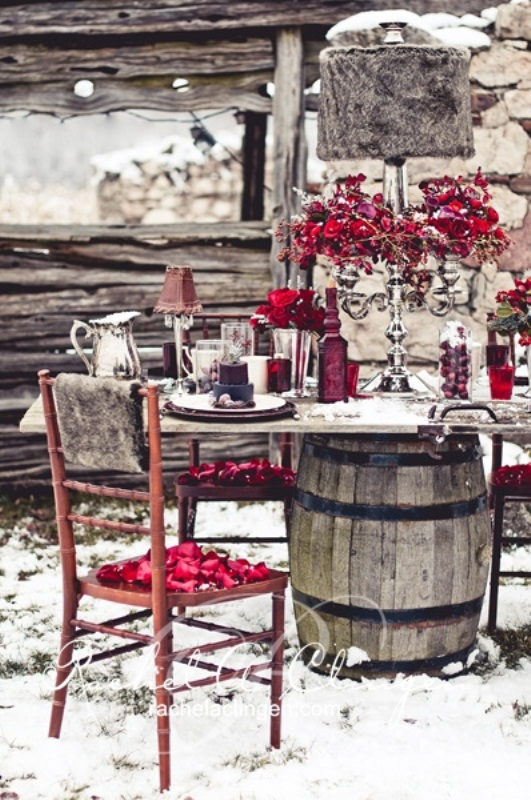a bright winter tablescape with red blooms, red cranberries, glasses, vases and cozy lamps with felt lampshades