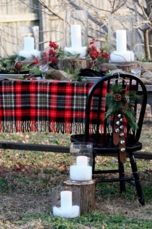 a rustic Christmas tablescape with a plaid tablecloth, evergreens, berries, bells and pillar candles on wood slices