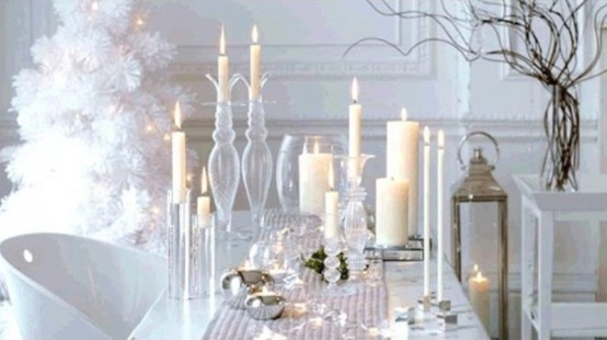 a chic white winter tablescape with a silver runner, bells, various candles and a large candle lantern
