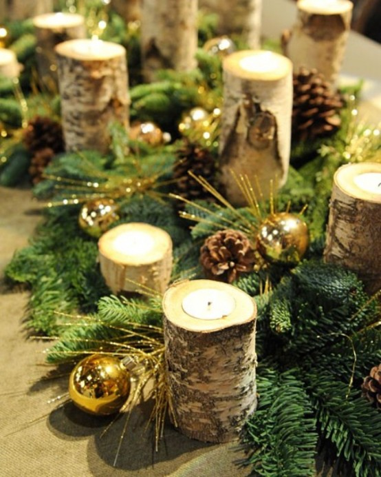 a Christmas table runner of evergreens, pinecones, metallic ornaments, tealight candles in branch candleholders