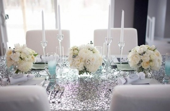 a silver and turquoise winter tablescape with white blooms, an ombre sequin tablecloth, mint glasses