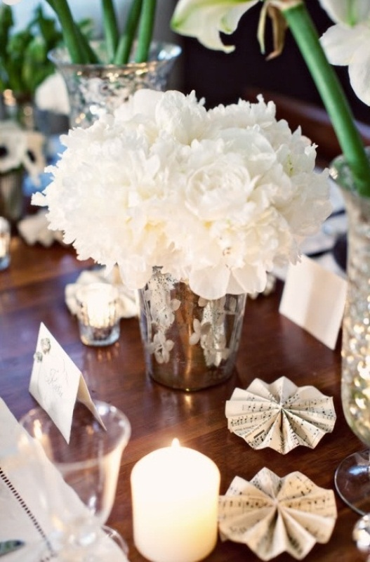 a lush white floral centerpiece in a silver bucket and pillar candles is a chic idea for a winter table setting