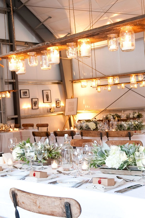stylish and cozy winter tablescapes with pale greenery and white blooms in crates, candles and jar lights over each table