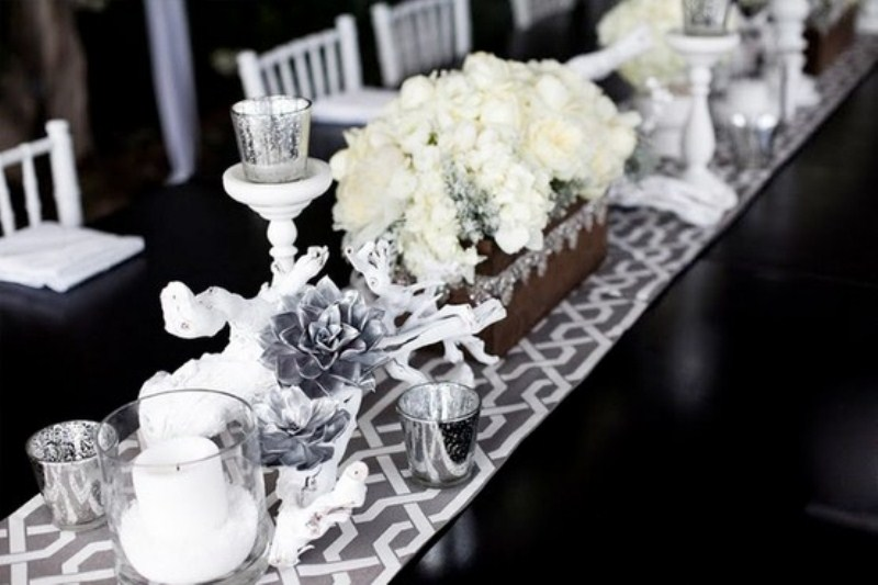 a black and white winter table setting done with a printed runner, white and silver blooms, candles and white branches