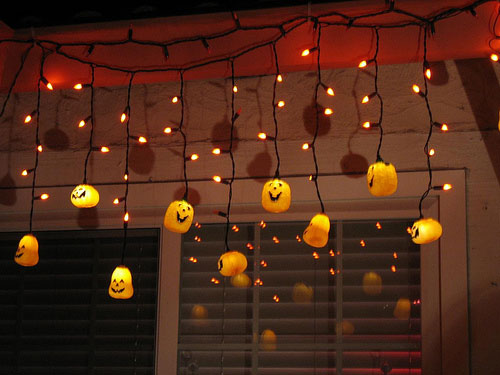 Cover some string lights with orange tissue paper balls with scary faces for a beautiful glowing display.