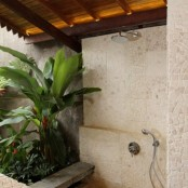 an outdoor shower all clad with stone tiles and planted tropical greenery
